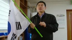 Un homme tient un drapeau sud-coréen.