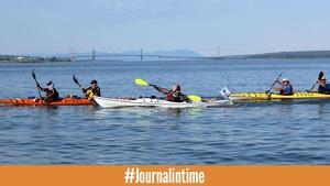 Trois kayakistes sur le fleuve, par une journée ensoleillée. On peut voir le pont de l'île d'Orléans derrière.