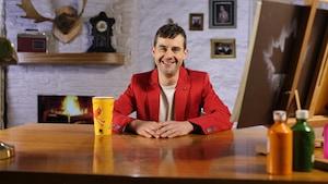 Doc Canada est assis derrière son bureau en bois. Il porte une veste rouge, un chandail beige. Dans le fond à droite, un feu de foyer brûle.