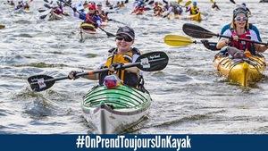 Une femme pagaie, assise dans un kayak. Elle sourit. À l'arrière-plan, on voit de nombreux kayakistes.
