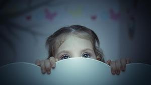 Une petite fille, à l'air effrayé, se cache derrière son lit.