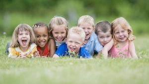 Un groupe d'enfants joue à l'extérieur.