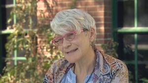 Gros plan sur Francine Proulx-Kenzle, elle porte une chemise bleue avec un foulard à motifs. Elle a les cheveux courts et porte des lunettes.