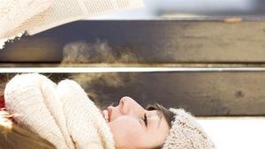 Femme lisant couchée sur un banc en hiver, à l'extérieur, avec un foulard, une tuque et des mitaines.