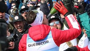 Alex Harvey boit du champagne à la bouteille devant la foule.