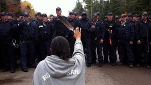 Amanda Polchies, agenouillée devant une rangée de policiers, tient une plume d'aigle.
