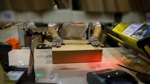 Un employé d'Amazon prépare un colis pour expédition dans un entrepôt de l'entreprise.