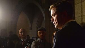 Le chef de l'opposition Andrew Scheer, debout et entouré de journalistes dans le foyer de la Chambre des communes, réclame la démission de Bill Morneau mercredi, 29 novembre 2017.