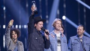 Le groupe Arcade Fire au moment de la remise du prix Juno pour l'album de l'année. Win Butler, le chanteur, tient la statuette haut dans les airs en s'adressant à la foule.