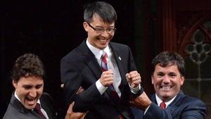 Le député Arnold Chan est soulevé par le chef du Parti libéral Justin Trudeau et le député Dominic LeBlanc, le 15 septembre 2014.