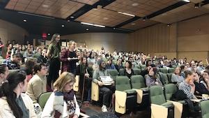 Des étudiants écoutent les étudiantes debout au micro.