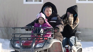 Une femme d'Attawapiskat sur un VTT avec des enfants.