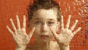 Un enfant prisonnier derrière une parois translucide.