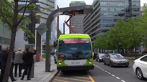 Un autobus qui affiche sur son écran frontal « 100 % électrique » est arrêté le long d'un trottoir. Un bras mécanique sort de son toit et est accroché à un poteau installé en bordure de trottoir.