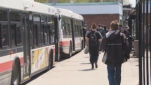 Des gens sur le quai qui embarquent dans des autobus au terminal du centre-ville de Trois-Rivières.