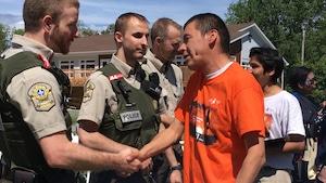 Des policiers de la Sûreté du Québec serre la main d'un homme lors de la Journée nationale des Autochtones