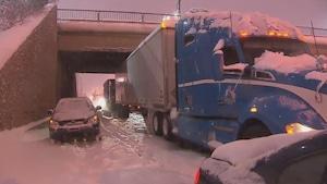 Un poids lourd bleu et une voiture immobilisés sur l'autoroute 13.