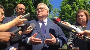 Le ministre Barrette entouré de micros de journalistes.