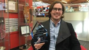 Eric Mourre est assis dans un banc et tient dans sa main le prix la Palme Bleue, qui est faite de verre bleuté mais transparent.