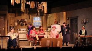 Neuf actrices, toutes blanches, jouent une scène de la pièce de théâtre Les Belles Soeurs.