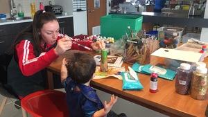 Une jeune femme fait du bricolage avec un enfant.