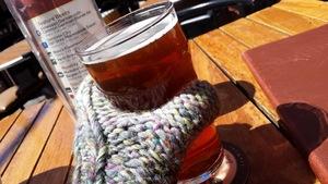 Une personne tient une bière avec sa main recouverte d'une mitaine.