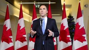 M. Morneau est debout au micro devant une série de drapeaux canadiens.