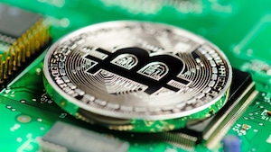 Un bitcoinn posé sur un micro processeur.