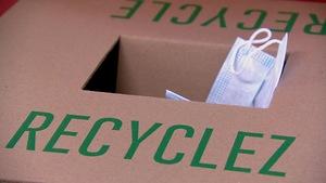 Plan rapproché d'une boîte de carton sur laquelle est inscrit le mot « RECYCLEZ »  en lettres majuscules vertes. Un masque obstrue partiellement la chute de la boîte.