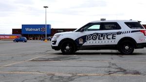 Une voiture de police est stationnée devant le Walmart.