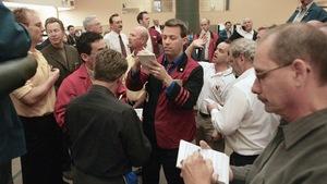Des hommes crient et lèvent la main dans une salle de marchés.
