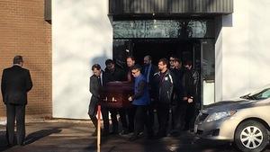 Les porteurs sortent le cercueil de l'église.