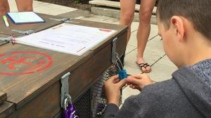 Un jeune garçon tente de débarrer un cadenas pour ouvrir un coffre.
