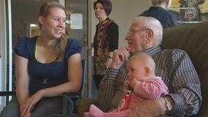 Un homme âgé tient un bébé dans ses bras. La mère de l'enfant, qui est assise à côté, sourit à l'homme âgé.