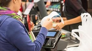 Une cliente inspecte sa facture à la caisse d'un grand magasin.