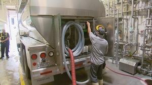 Deux travailleurs s'affairent à transférer l'eau d'un camion-citerne.