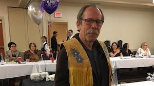Dans la photo, on voit Alan Rollins, le chef du conseil scolaire Kee Tas Kee Now debout avec en arrière plan des gens assis autour d'une table.