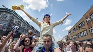 Un homme portant une coupe et un chapeau de gaulois sur les épaules d'un autre homme au milieu d'une foule