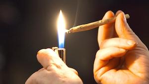 Une personne s'allume un joint de marijuana.