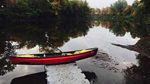Un canot posé sur un quai. Paysage d'automne.
