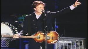 Paul McCartney s'adresse à la foule en tenant sa basse.
