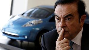 Carlos Ghosn devant une voiture.