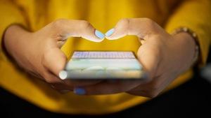 Les mains d'une femme tiennent un téléphone cellulaire.