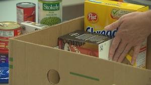 À Trois-Rivières, l'organisatrice communautaire du Centre Jean-Noël Trudel, Marie Hallé, place de la nourriture dans une boîte.