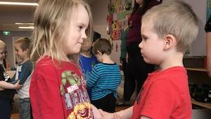 Deux enfants se tiennent debout, face à face. D'autres enfants se tiennent debout derrière.
