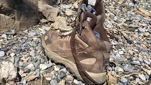 Des chaussures de randonnée sur des pierres. On aperçoit des chaussettes à l'intérieur.