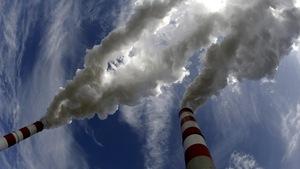Des cheminées industrielles d'où on peut voir s'échapper de la fumée.