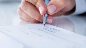 Une main tenant un crayon signe un chèque.