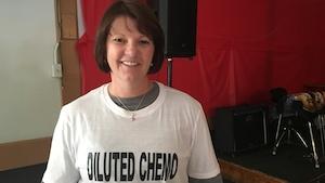 On peut voir une dame souriante avec un T-Shirt portant l'inscription DILUTED CHEMO.