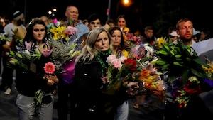 Des dizaines de personnes marchent avec des bouquets de fleurs dans les mains.